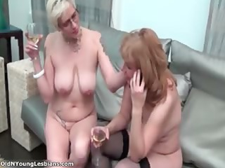 two naughty cougar homosexual women are drinking