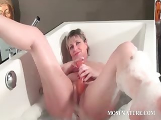 horny mature pleases into bathtub